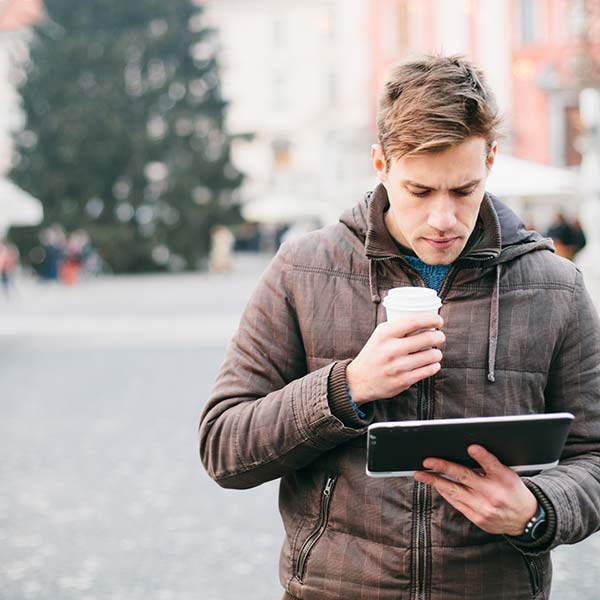 A young man in a winter coat, standing on a city square during the Christmas time, is watching his tablet and drinking coffee