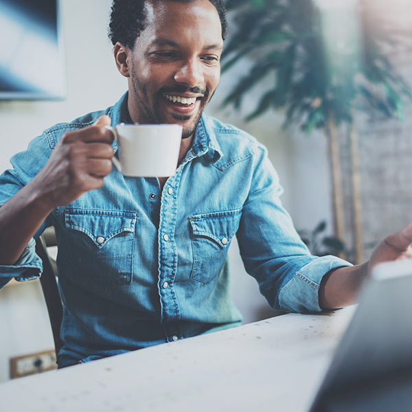 A happy young black man wearing a blue shirt is looking at his computer and drinking a cup of coffee, sitting in his office