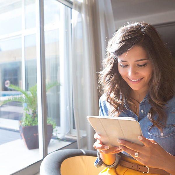 A happy young woman in a blue shirt and a yellow pant is smiling and looking at her tablet, sitting next to a window