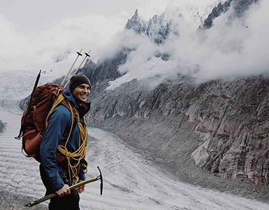 Hiker standing in front of a mountain smiling ready to conquer the peak