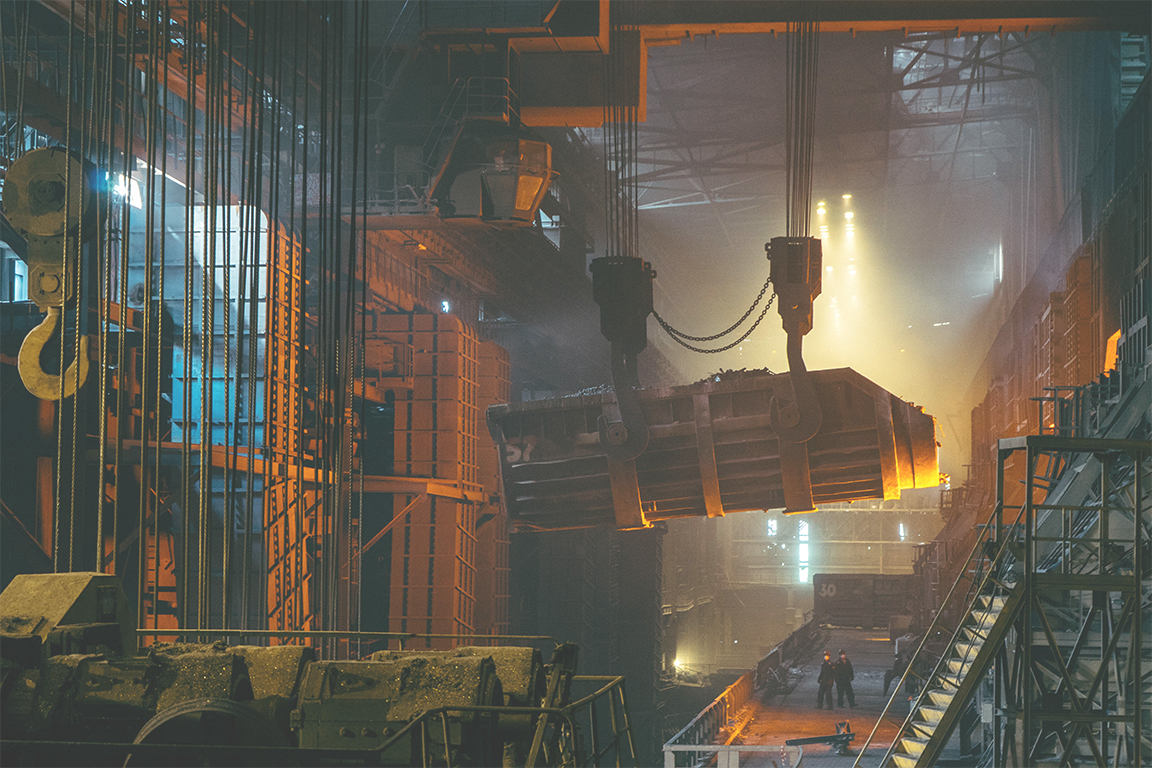 A dark steel factory with some workers in the background