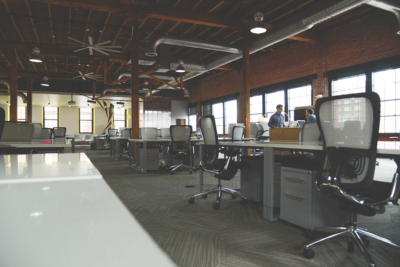 A modern open workspace full of desks and some people working together
